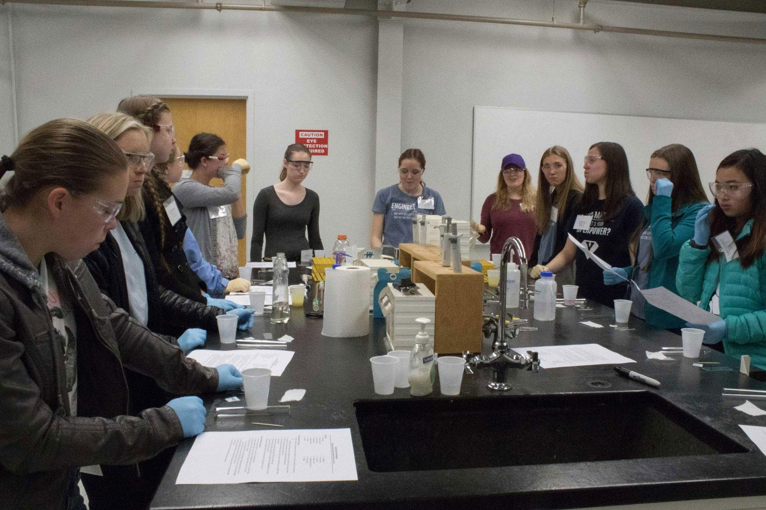 Group of Females around table looking at scientific equipment