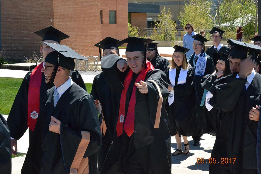 Graduates walking down sidewalk