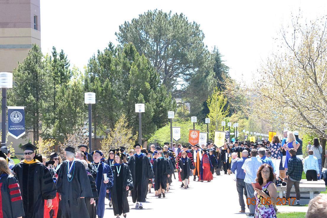Graduates and Professor walking down sidewalks